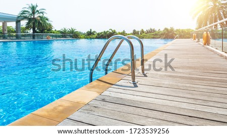 Swimming pool with stair and wooden deck. #1723539256
