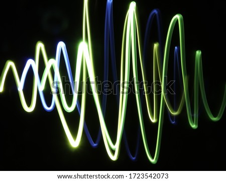 Blue, yellow and green light painting photography forming an electrocardiogram trace (ECG) against a black background (light painting, pulse trace, heart rate line). Neon light painting photography.