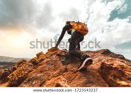 Success woman hiker hiking on sunrise mountain peak - Young woman with backpack rise to the mountain top. Discovery Travel Destination Concept Royalty-Free Stock Photo #1723543237