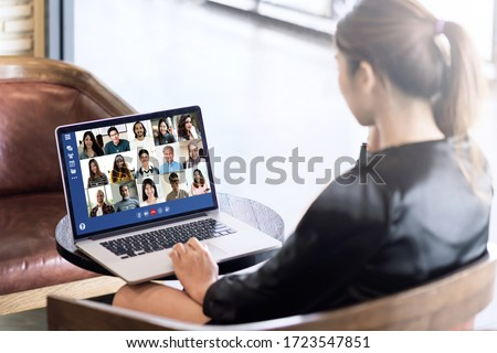Back view of young asian business woman work remotely at home video conference remote call to corporate group. Meeting online,videocall, group discuss online concept with screen of teamwork on laptop. #1723547851