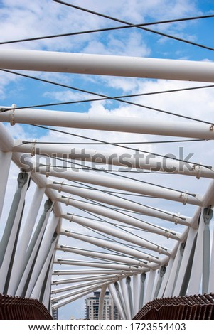fragment of the metal construction of white pipes against a blue sky with clouds #1723554403