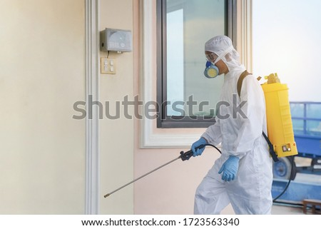 Specialist man in protective suit spraying disinfectant coronavirus cells epidemic. He Cleaning decontamination in house, shelter and public place as a prevention against COVID-19. #1723563340