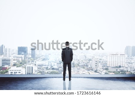 Businessman standing on building. City background with copy space. Success and vision concept Royalty-Free Stock Photo #1723616146