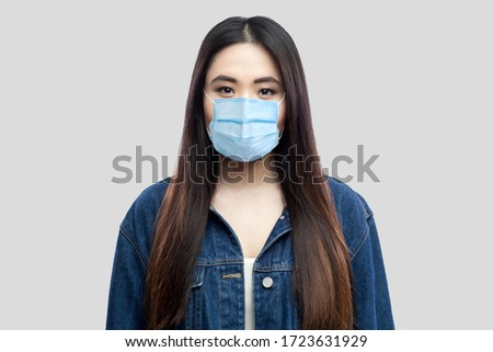 Portrait of beautiful brunette asian young woman with surgical medical mask in blue denim jacket standing and looking at camera. indoor studio shot, isolated on light grey background. #1723631929