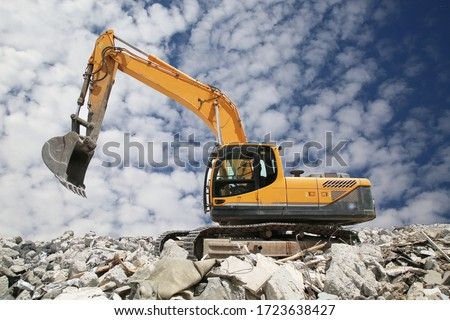 Excavator digs the ground for the foundation and construction. Excavator   working demolition site.Heavy excavator with shovel standing on hill with rocks Royalty-Free Stock Photo #1723638427