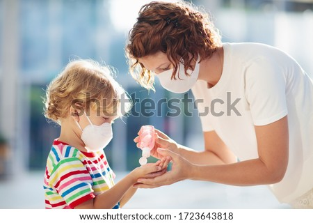 Family with kids in face mask in shopping mall or airport. Mother and child wear facemask during coronavirus and flu outbreak. Virus and illness protection, hand sanitizer in public crowded place. #1723643818