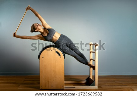 Pilates trainer exercises on a pilates barrel. Body training, perfect body shape and posture correction opporno motor apparatus. Copy space. Royalty-Free Stock Photo #1723669582