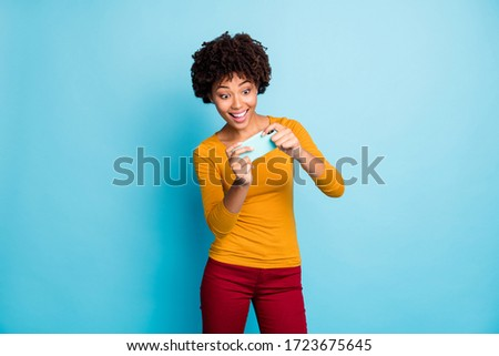 Portrait of her she nice attractive lovely glad excited addicted cheerful cheery wavy-haired girl using cell playing online game isolated over bright vivid shine vibrant blue color background #1723675645
