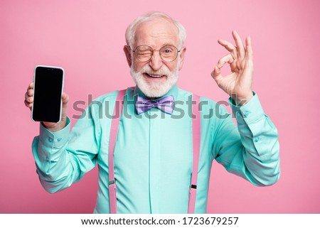 Portrait of energetic positive old man hold new cellphone show okay sign recommend choose good modern technology wear teal turquoise shirt violet bow tie isolated pastel pink color background #1723679257