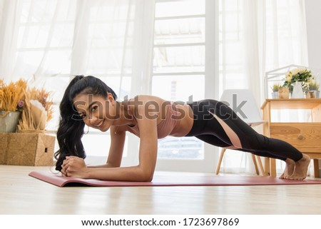 A beautiful Asian woman's fitness at home instead of going to the gym. She doing a plank on the yoga mat. She wears sportswear. Exercise concept for good shape #1723697869