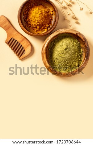 Henna powder in a wooden bowl and a wooden comb on a beige background top view. Natural hair care. Henna hair dye.