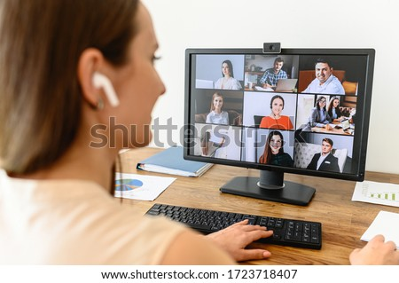Video call, video meeting. A young woman connect with a many employees together via video, she sits at office space and looks at webcam, rear view #1723718407