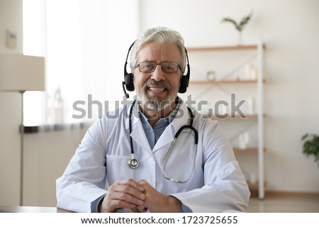 Smiling senior old doctor wears headset looking at camera. Remote online medical chat consultation, tele medicine distance services, virtual physician conference call, telemedicine concept. Portrait. #1723725655