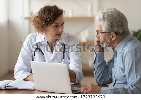 Young female professional doctor physician consulting old male patient, talking to senior adult man client at medical checkup visit. Geriatric diseases treatment. Elderly medical health care concept Royalty-Free Stock Photo #1723725679