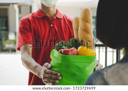 food delivery service man with protection face mask in red uniform holding fresh food set bag to customer at door home, express delivery, quarantine, virus outbreak, takeaway food delivery concept #1723729699