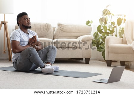 Young Black Guy Meditating In Front Of Laptop At Home, Watching Yoga Tutorials Online, Sitting In Lotus Position In Living Room, Copy Space #1723731214