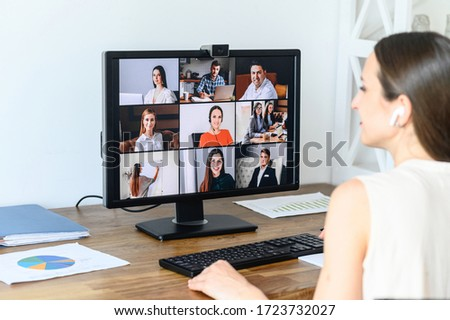 Video conference with colleagues, coworkers. A young businesswoman using application on pc in office for online conversation with coworkers. Back view #1723732027