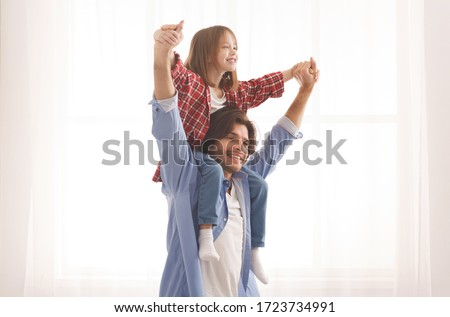 Cheerful dad holding his happy little girl on shoulders, carrying her hands over white background, copy space #1723734991