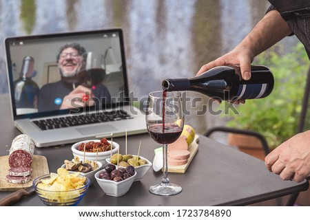 Lockdown aperitif video call party. Adult men are making a pre-meal aperitif with snacks, wine, and Italian appetizers together at home using teleconference platform apps during COVID-19 restrictions #1723784890