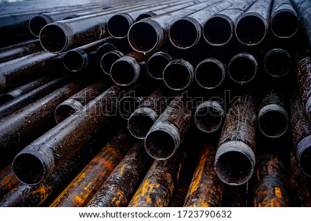 Oil Drill pipe. Rusty drill pipes were drilled in the well section. Downhole drilling rig. Laying the pipe on the deck. View of the shell of drill pipes laid in courtyard of the oil and gas warehouse #1723790632