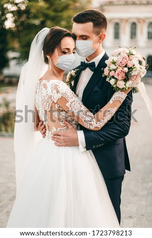 Young loving brides hugging in the city in medical masks with a bouquet of roses during quarantine on their wedding day. Coronavirus, disease, protection. #1723798213