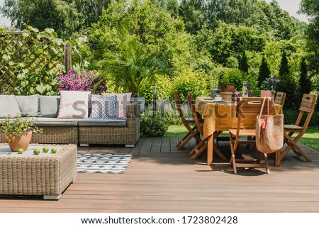 Dining table covered with orange tablecloth standing on wooden terrace in green garden #1723802428