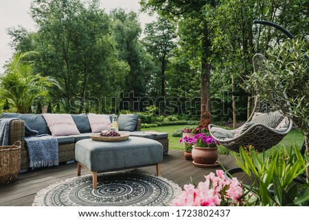 Classy furniture on wooden terrace in green beautiful garden #1723802437