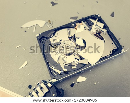 Broken computer hard disk on a table - complete data destruction. Royalty-Free Stock Photo #1723804906