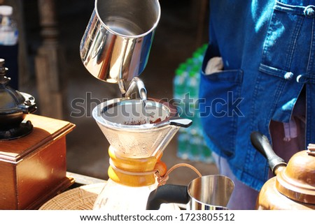 Dripping coffee in the morning, crop picture closeup man pouring hot water into coffee filter, human with many tools for making beverage in slow life concept