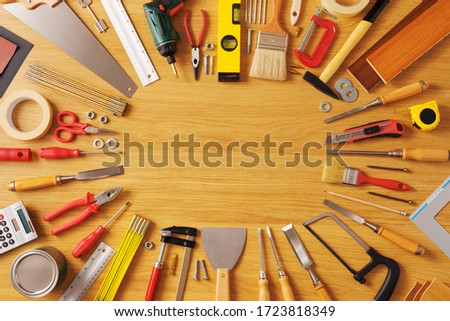 DIY and home improvement banner with work and construction tools on a wooden workbench top view, copy space at center Royalty-Free Stock Photo #1723818349