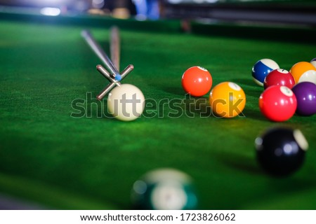 Man's hand and Cue arm playing snooker game or preparing aiming to shoot pool balls on a green billiard table. Colorful snooker balls on green frieze #1723826062