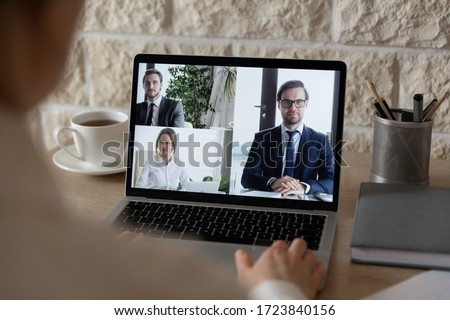 Rear view of businesspeople speak talk on video call using laptop gadget, discuss ideas together, employee have webcam conference conversation with business partners or clients on computer in office #1723840156