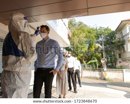 Security guard in PPE suit uses infrared thermometer measuring temperature with European staff scanning for Coronavirus or Covid-19 symptom at office entrance. International medical healthcare system #1723848670
