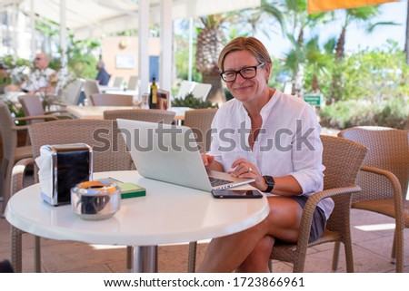 Woman sitting in a coffee bar working on her laptop. She is looking in to the camera with a happy smile. #1723866961