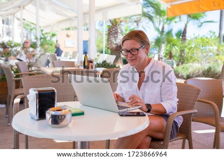 Woman sitting in a coffee bar working on her laptop. She is looking down on the screen. #1723866964