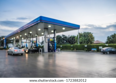 Abstract blur photo of car refueling on gas station at sunset. Pump gasoline gauge oil in the evening. This photo can be used for automotive service industry or unleaded transportation concept Royalty-Free Stock Photo #1723882012