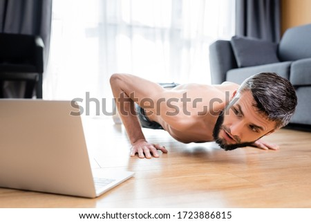 Selective focus of shirtless sportsman doing push ups near laptop on floor #1723886815