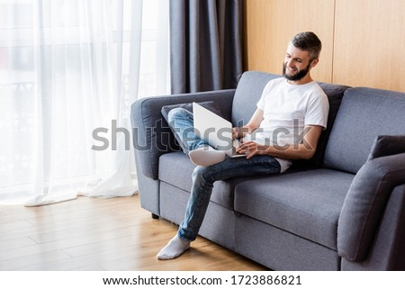 Positive teleworker working on laptop on couch at home #1723886821
