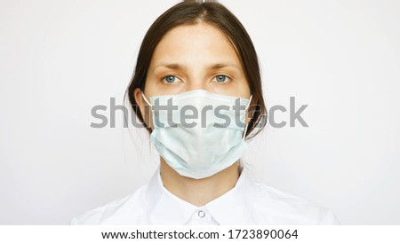 One pretty nurse with a protective mask looks into the distance #1723890064