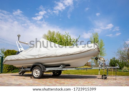 Big modern inflatable motorboat ship covered with grey or white protection tarp standing on steel semi trailer at home backyard on bright sunny day with blue sky on background. Boat vessel storage Royalty-Free Stock Photo #1723915399