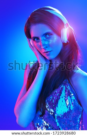 Party and holiday style. Pretty girl with shiny make-up and shiny dress listening to music in headphones and dancing in blue and pink light. #1723928680
