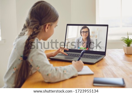 Online education of children. Girl schoolgirl teaches a lesson online using a laptop video chat call conference with a teacher at home. #1723955134