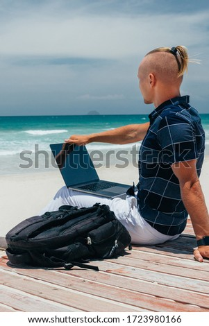 guy Looks at the sea side using a laptop, sitting on the seashore on a sandy beach. Businessman working on remote work on a journey. freelancer makes a content work plan #1723980166