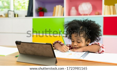 Young African American kid girl studying using digital tablet, preschool child study at home school. Children education, self isolation, coronavirus outbreak social distancing or homeschooling concept #1723981165