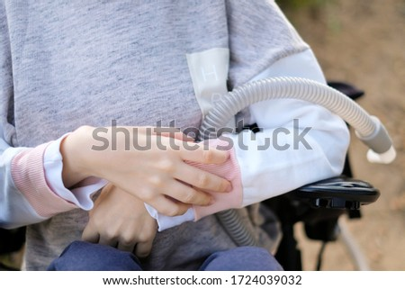 Hands of a disabled person with muscular dystrophy holding a ventilator for deep breathing, concept, background Royalty-Free Stock Photo #1724039032