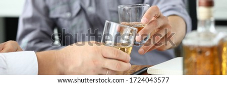Businessman put down documents and drink alcohol. Men sit at home during quarantine and drink alcohol. Communication business partners and solving important issues. Violation rules self-isolation #1724043577