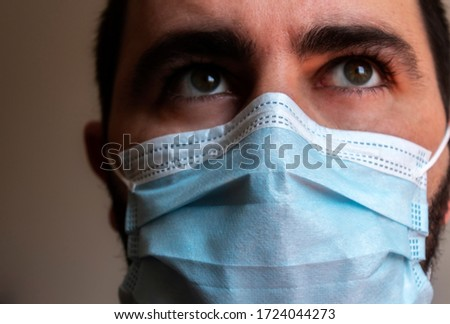 Portrait of a male with blue mask in an interior space. Psychological portrait of the effects of the quarantine for the Coronavirus crisis #1724044273