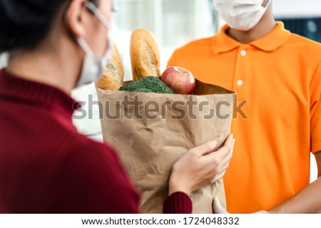Asian deliver man wearing face mask in orange uniform handling bag of food, groceries, fruit give to woman costumer in front of the house. Postman and express grocery delivery service during covid19. #1724048332