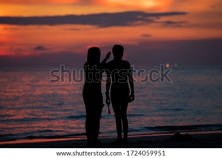 Man and women standing at the beach in the twilight time.Silhouett picture style.