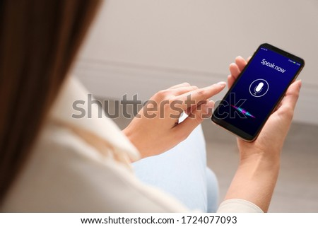 Woman using voice search on smartphone indoors, closeup #1724077093
